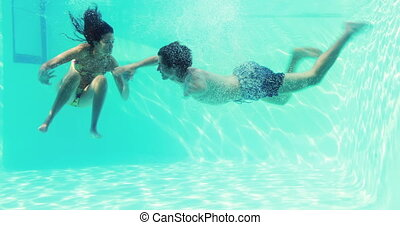 Happy couple jumping in swimming po