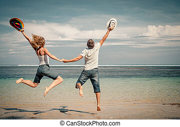happy couple jumping on the beach at the day time