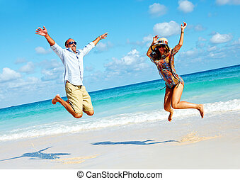 Happy couple jumping on the beach.