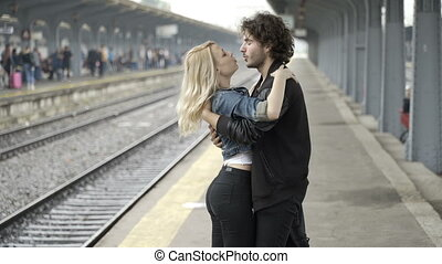 Happy couple kissing and walking hand in hand on railway station