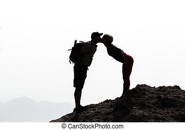 Happy couple kissing on mountain summit