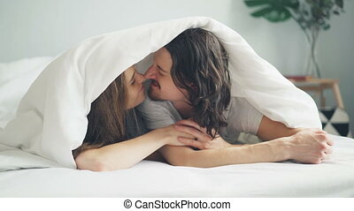 Happy couple kissing rubbing noses under blanket lying on...