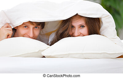 Happy couple laughing in bed peeking out from under blanket