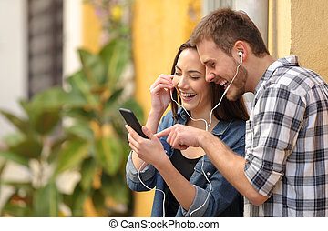 Happy couple laughing listening to music online