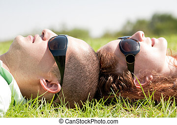 Happy couple laying on a lawn and looks