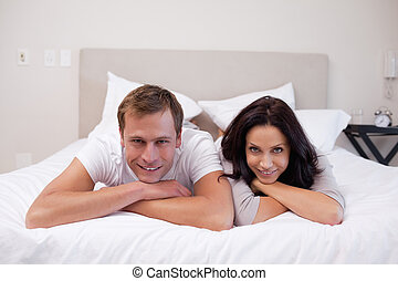 Happy couple laying on the bed together