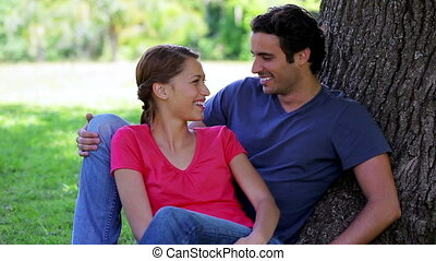 Happy couple leaning against a tree
