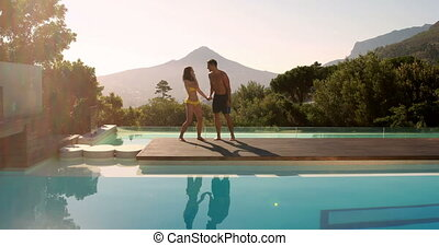 Happy couple leaping into the outdoor swimming pool on their...