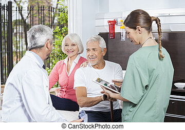 Happy Couple Listening To Doctor While Nurse Holding Digital Tab