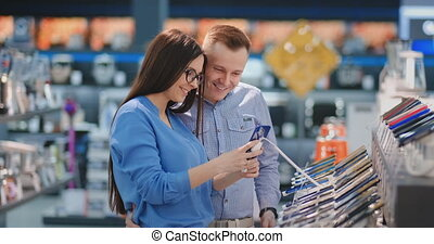 Happy couple looking at a new digital camera at an electronics shop