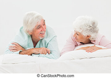 Happy couple looking at each other in bed