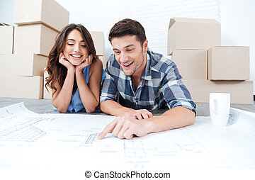 Happy couple looking at new house blueprints