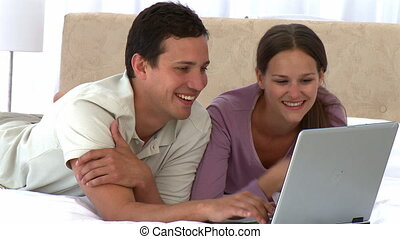 Happy couple looking at the laptop