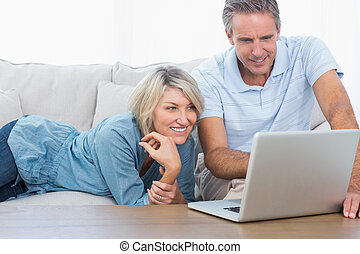 Happy couple looking at their laptop