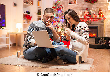 Happy couple looking for christmas gifts on internet