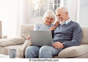 Happy couple looking through photos from their trip on laptop