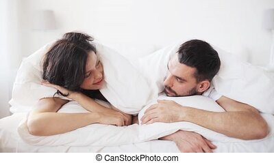 happy couple lying in bed at home
