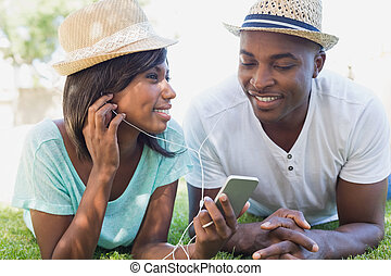 Happy couple lying in garden together listening to music on...