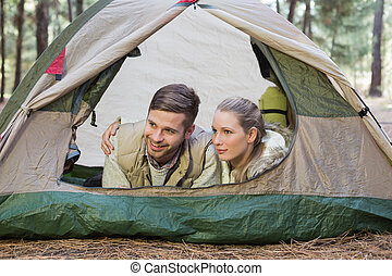 Happy couple lying in tent after a hike and looking away in...