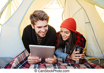 Happy couple lying in tent and using tablet computer -...