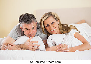 Happy couple lying on a bed and looking at camera