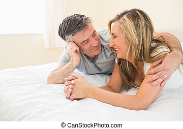 Happy couple lying on a bed and looking each other