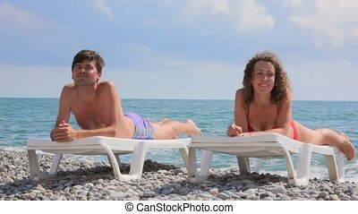 happy couple lying on beach beds in pebble, clouds and sea in background