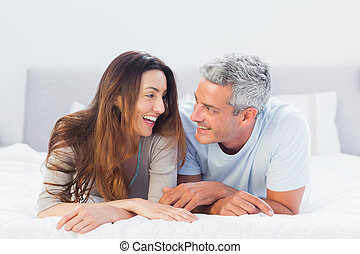 Happy couple lying on bed talking together
