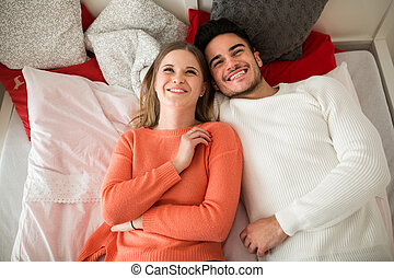 Happy couple lying on bed together laughing
