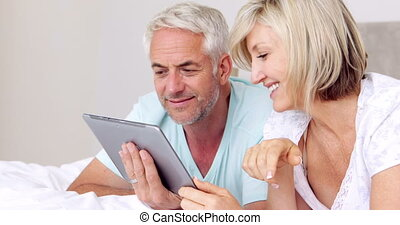Happy couple lying on bed using tablet