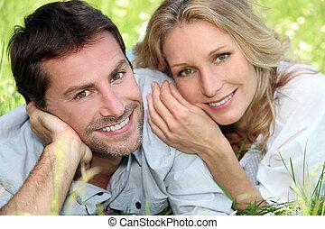 Happy couple lying on grass