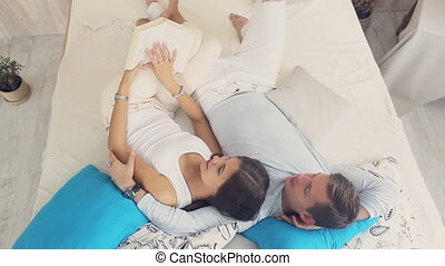 happy couple lying on the bed and reading a book