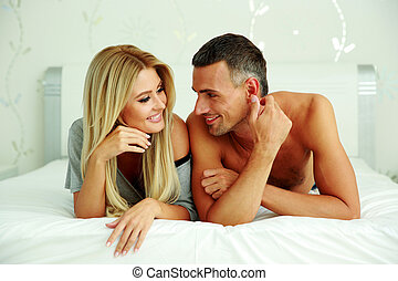 Happy couple lying on the bed at home