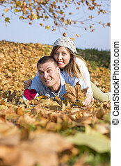 Happy couple lying on the fallen leaves