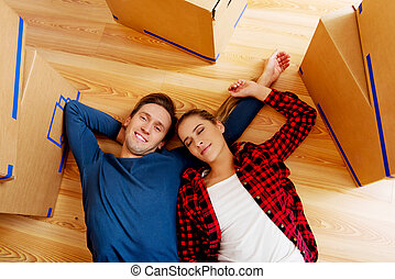 Happy couple lying on the floor in new home with cordboard boxes around