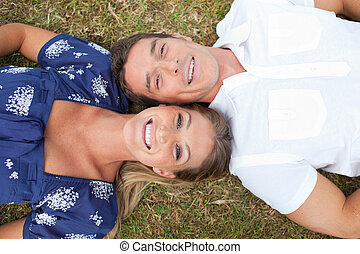 Happy couple lying on the grass in a park