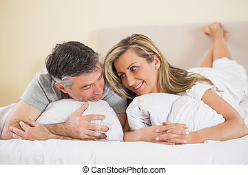 Happy couple lying on their bed and looking at each other