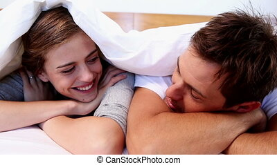Happy couple lying under the duvet at home in bedroom