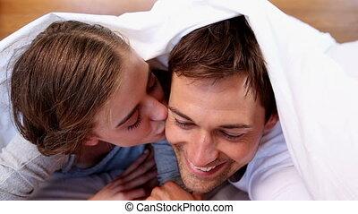 Happy couple lying under the duvet