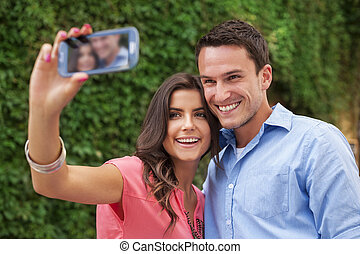 Happy couple making a photo of themselves
