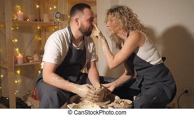 Happy couple making clay jug on potter's wheel.