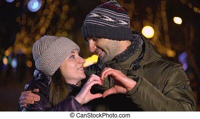 Happy couple making heart shape with hands gesturing...