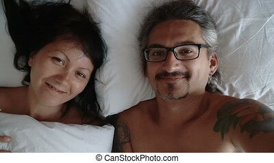 Happy couple making selfie in the bed.