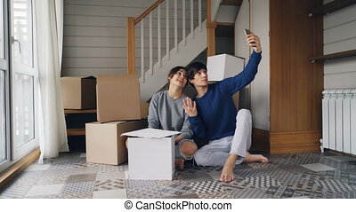 Happy couple man and woman are making online video call with smartphone after relocation. They are greeting friends, showing new house keys and boxes, chatting and smiling.