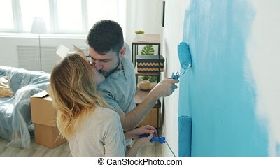 Happy couple young man and woman are painting wall at home talking kissing having fun together enjoying renovation in apartment. Youth and housing concept.