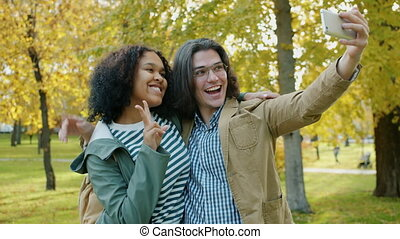 Happy couple man and woman taking selfie with smartphone in autumn park