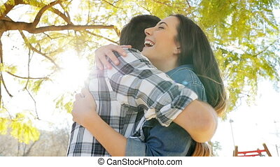 Happy couple meeting and hugging in a park