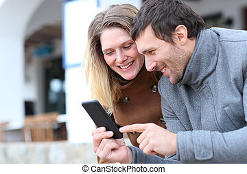 Happy couple of adults checking smart phone in winter