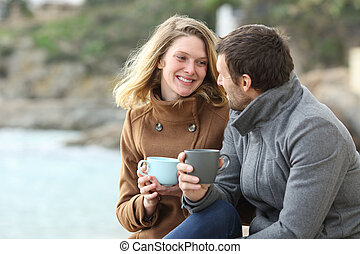 Happy couple of adults talking in winter on the beach