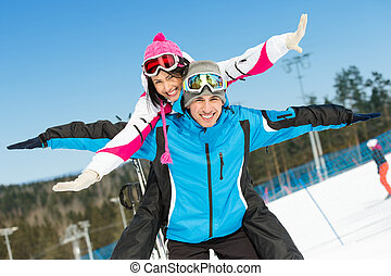 Happy couple of alpine skiers have fun
